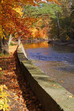Glorious Fall Colors by Water. Fall scene river, retaining stone wall, glorious trees, splendid colors royalty free stock photos