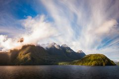 Glorious Light early in the Morning on Lake Manapouri. Glarious Morning at Lake Manapouri with the sunlight bringing golden hues in the crown of clouds raising Royalty Free Stock Images
