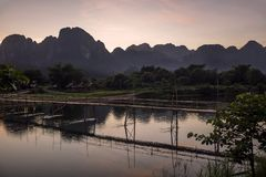 Glorious sunset over the mountains that dominate Vang Vieng overlooking the Nam Song river and the wooden bridge, Laos. Asia stock images