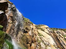 Glorious waterfall at Porthcurno beach, Cornwall looking up into deep blue sky Stock Image