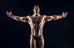 Glory of champion. Handsome muscular bodybuilder posing over black background. Glory of the champion stock photos