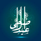 Glossy Arabic text for Eid-Al-Adha celebration. Glossy white Arabic Islamic calligraphy of text Eid-Al-Adha on floral design decorated shiny blue background for Stock Photography