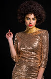 Glossy arrogant diva. Is awashed with money, because she spends a lot for her impeccable style. Golden elements on her body, short dress with sequins. Serious Stock Images