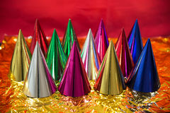 Glossy birthday hats. Glossy birthday hats on golden and red background Royalty Free Stock Image