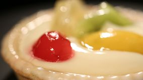 Glossy cake high in sugar and decorated with canned fruit, unhealthy dessert stock footage