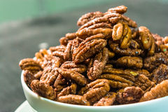 Glossy Candied Pecans. Candied Pecans spread out on a plate Stock Images