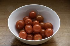 Glossy cherry tomatoes in a white bowl. royalty free stock photography