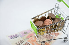 Glossy and colorful coins with banknotes in the shoping cart. Financial item. Isolated background Royalty Free Stock Images
