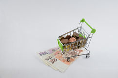 Glossy and colorful coins with banknotes in the shoping cart. Financial item. Isolated background Stock Image