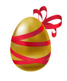 Glossy golden egg tied with red ribbon and bow. Stock Photo