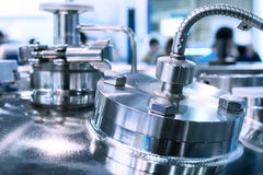 Glossy metal flanges on the body of the pharmaceutical reactor. Close-up photo, selective focus. Abstract industrial background Royalty Free Stock Photo