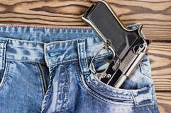 Glossy metal silver pistol in front pocket of blue jeans on old rustic wooden planks royalty free stock image
