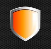 Glossy orange shield. On hexagon mesh black background Stock Images