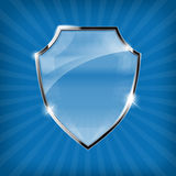 Glossy security shield on blue background Royalty Free Stock Photo
