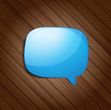 Glossy speech bubble on wood background Stock Images