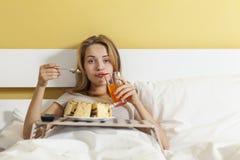 Glotonería del día, muchacha adolescente que come una torta y una soda de las bebidas Foto de archivo libre de regalías