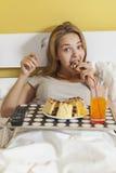 Glotonería del día, muchacha adolescente que come una torta y una soda de las bebidas Imágenes de archivo libres de regalías