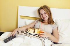 Glotonería del día, muchacha adolescente que come una torta y una soda de las bebidas Foto de archivo