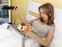 Glotonería del día, muchacha adolescente que come una torta y una soda de las bebidas Imagen de archivo libre de regalías
