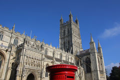 Gloucester Cathedral, behind traditional post box, with a blue s Stock Images
