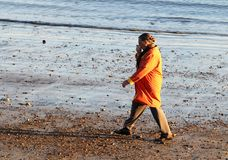 A woman in the orange coat walking on the beach at early spring in Gloucester, Massachusetts stock image