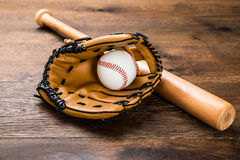 Glove With Baseball And Bat. Close-up Of Leather Glove With Baseball And Bat On Wooden Table Royalty Free Stock Photo