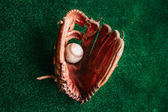 Glove of the baseball catcher and the ball. Old leather glove of the baseball catcher and the ball Stock Photo