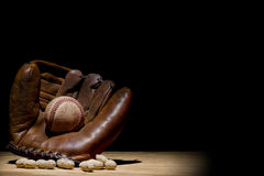 Glove and Baseball. Old time glove and baseball in spotlight with a few peanuts Stock Photo