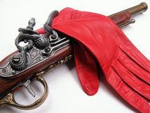 Glove challenge. An old gun and a red glove for a challenge Royalty Free Stock Images