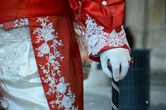 Glove : detail of Venetian Carnival. A hand wearing a white glove, with a ring poses on a walking stick, as if it were a scepter Royalty Free Stock Photo