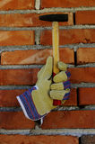 Glove and hammer. Unvisible hand in a glove holding a hammer against red brick wall royalty free stock photography