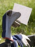 Glove Holding Blank Card. Gardeners Glove over Hand Shovel Holding Blank Card Stock Photos