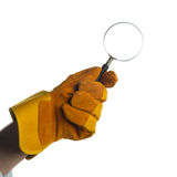 Glove holding a magnifying glass. A yellow/brown gauntlet holding a magnifying glass Royalty Free Stock Photo