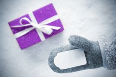 Purple Gift, Glove, Copy Space, Snowflakes. Glove With Label Copy Space For Advertisement. Purple Gift Or Present On Snow In Background. Seasonal Greeting Card Royalty Free Stock Photography