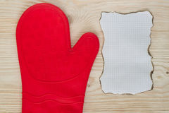 Glove and sheet of paper. Mitten for hot meals with a sheet for recipes Stock Photo