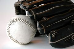 Glove and Softball. A black leather ball glove with a softball in the pocket royalty free stock images