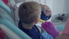 Gloved dentysta wręcza sprawdzać tooths mały beztroski chłopiec obsiadanie w krześle pokazuje on lustro w górę zbiory wideo