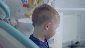 Gloved dentysta wręcza sprawdzać tooths mały beztroski chłopiec obsiadanie w krześle pokazuje on lustro w górę zbiory