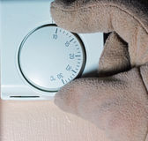 Gloved hand altering heating thermostat. Royalty Free Stock Photography