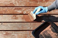 Free Gloved Hand Applying Stain On Home Cedar Wooden Deck Boards Stock Photos - 216200033