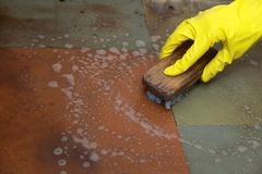 Gloved hand cleaning of dirty filthy floor Stock Photos
