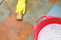 Gloved hand cleaning of dirty filthy floor Royalty Free Stock Images