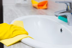 Gloved hand cleaning sink edge Stock Images