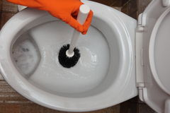 Gloved hand cleaning toilet bowl using brush Stock Photo