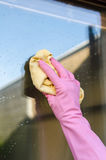 Gloved hand cleaning window Stock Images