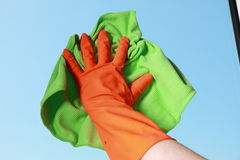 Gloved hand cleaning window with rag Stock Image