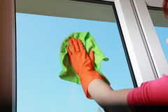 Gloved hand cleaning window with rag Royalty Free Stock Images
