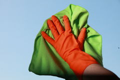 Gloved hand cleaning window with rag Royalty Free Stock Photography