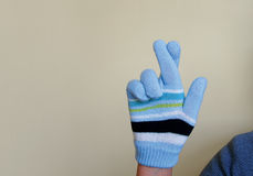 Gloved hand crossing fingers Stock Photography