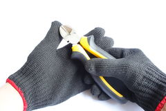 Gloved hand and cutting pliers Royalty Free Stock Photography